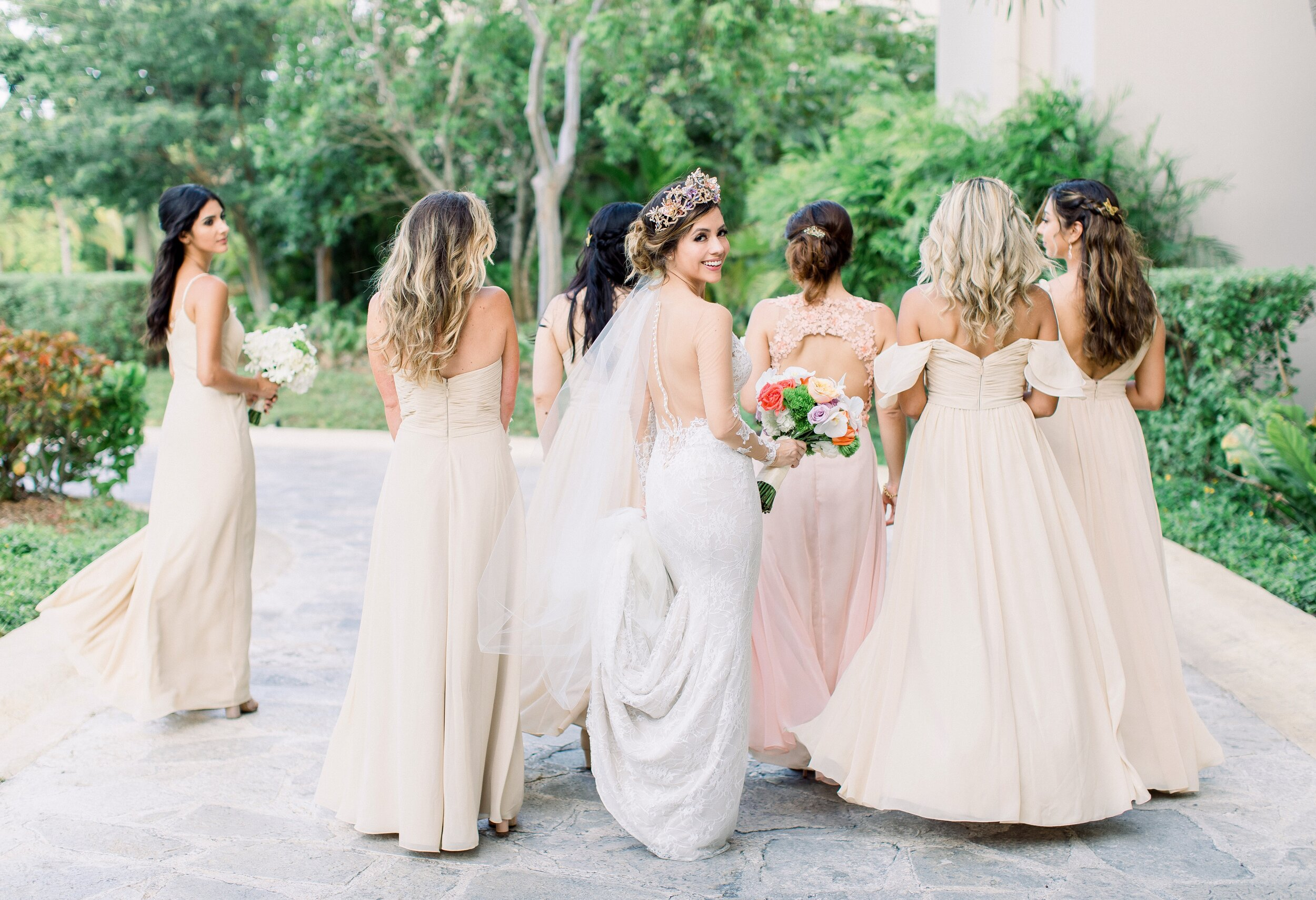 bride wears a lace wedding gown and bridesmaids wear blush bridesmaids dresses to mexico destination wedding