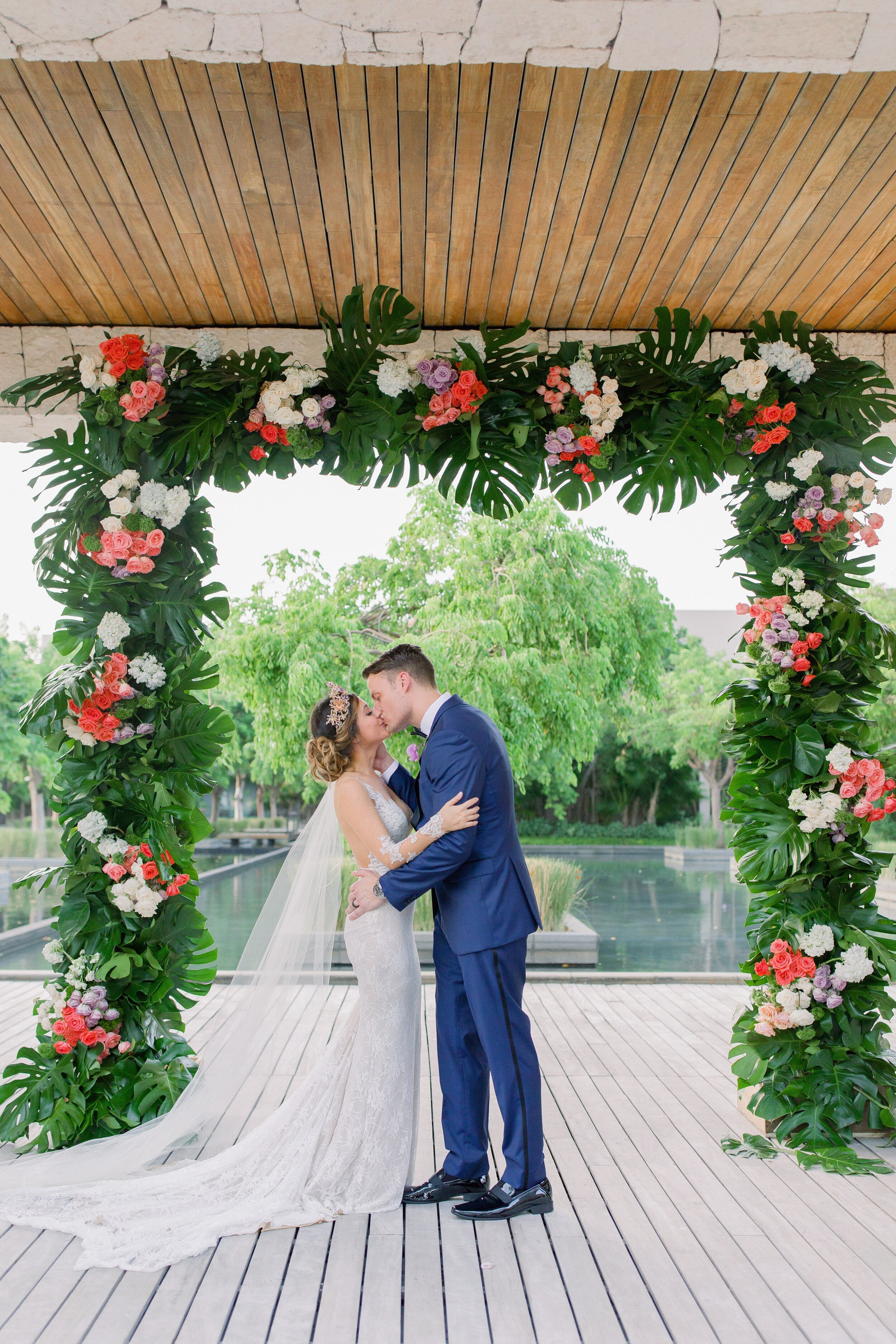 bride and groom married under green palms and colorful floral at tropical destination wedding