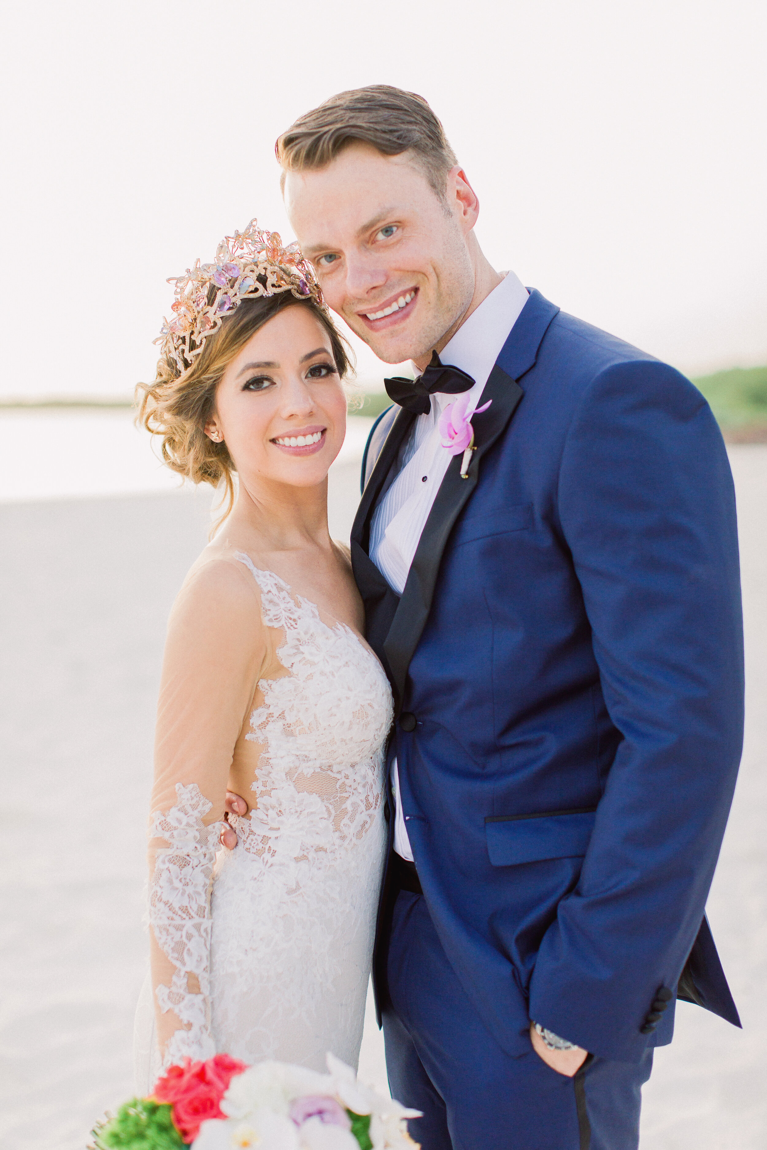 bride and groom at beach wedding in mexico bride wearing a long sleeve lace gown with colorful crown by maria elena headpieces