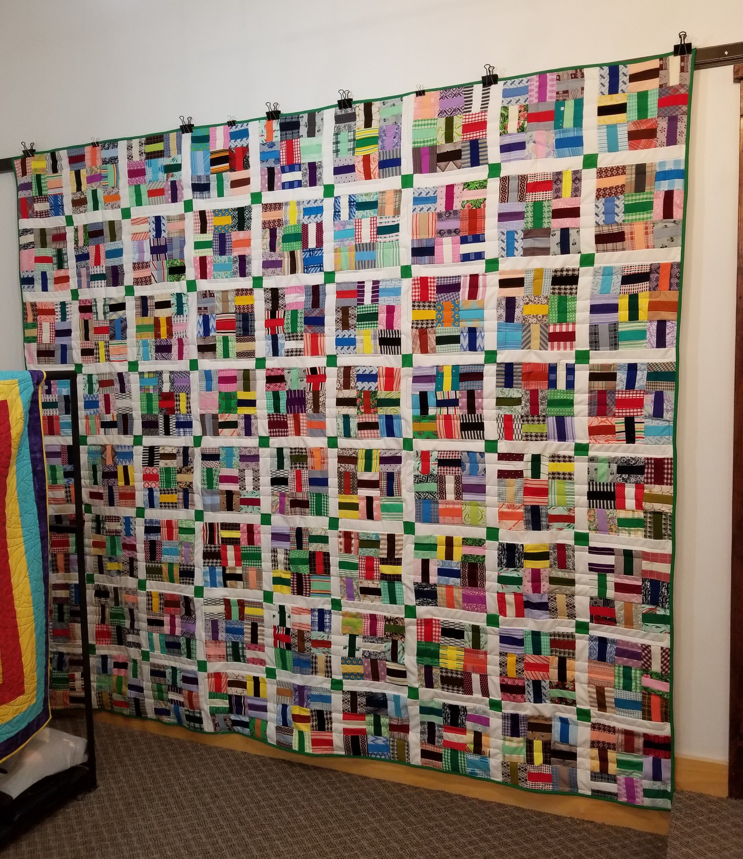 This quilt so heavy, we had to use additional clips to hang from the bar.