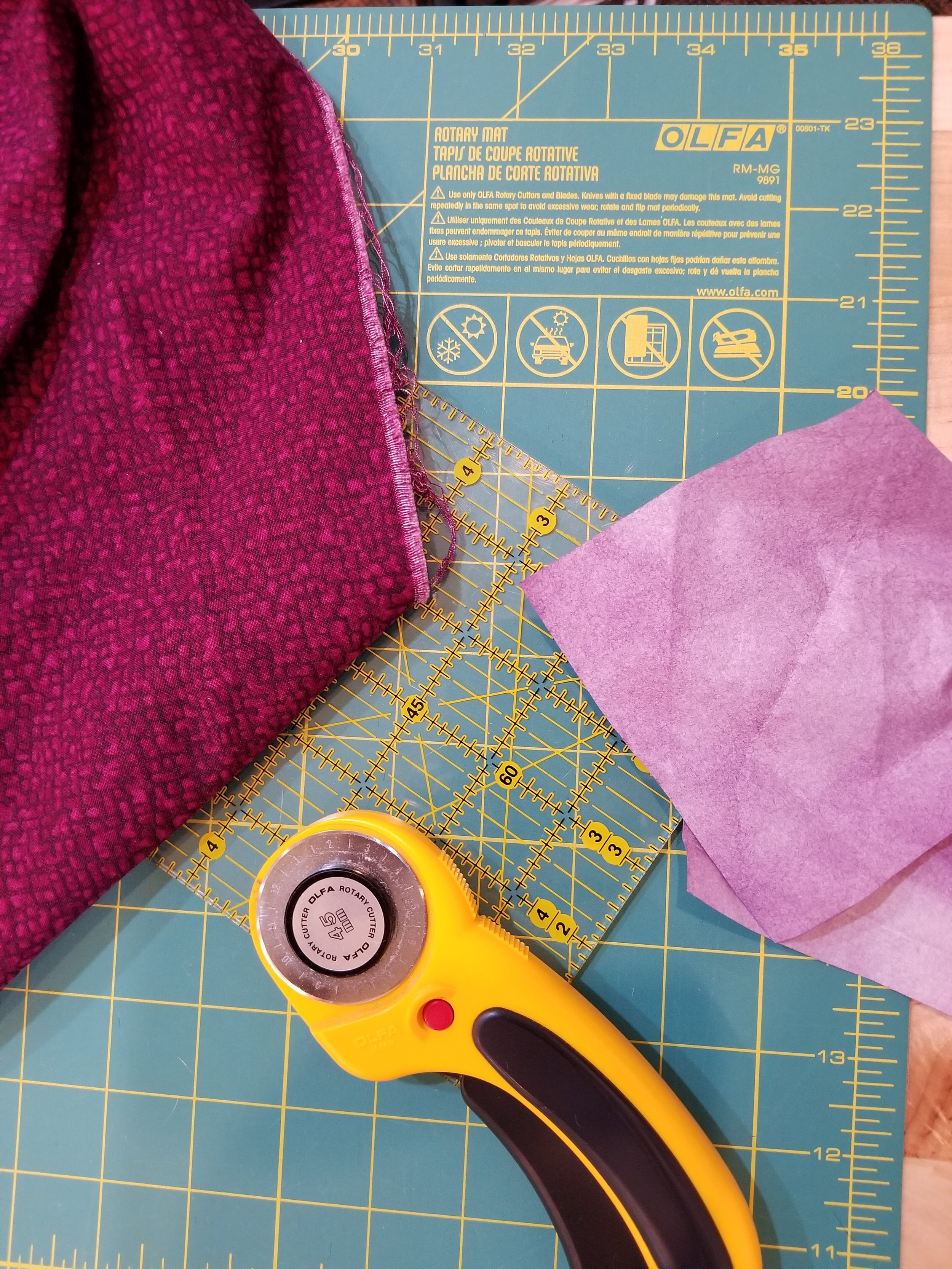 The ruler and rotary cutter takes care of the frayed edges and selvages. This colour catcher took care of pulling the dye out so no future bleeds onto other laundry items or the rest of the quilt.
