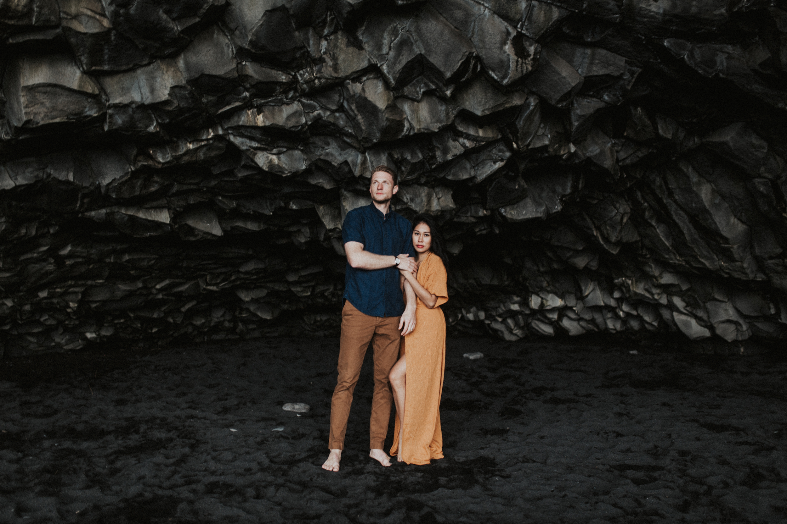 Stunning couple in orange dress and blue shirt in Icelandic caves in Vik.jpg