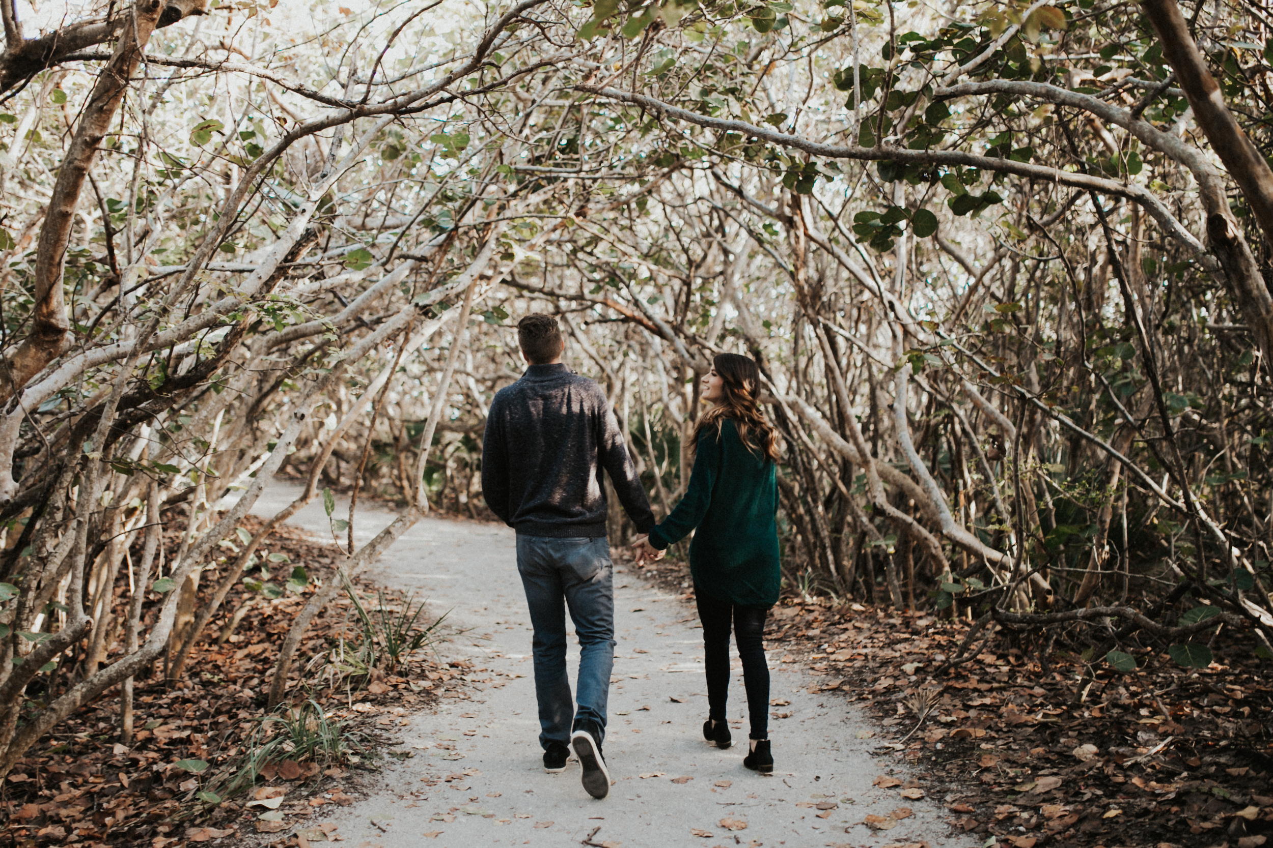 Couple walking through Florida shrubs.jpg