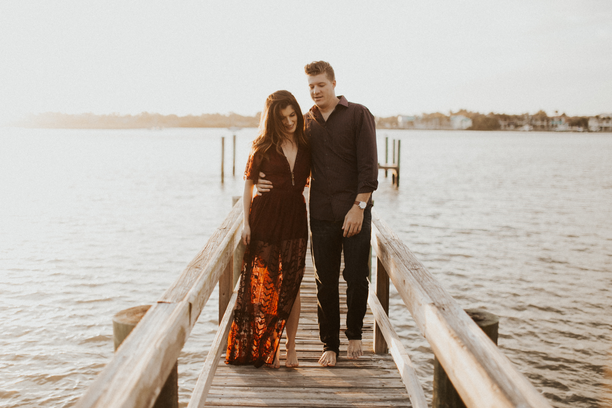 sunlit couple on boat dock in south florida engagement session.jpg