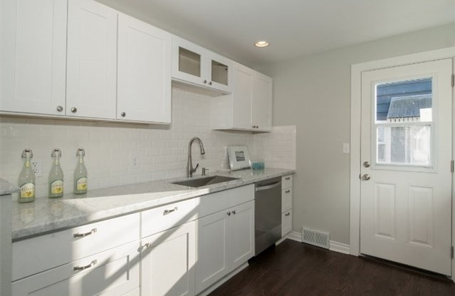 After: A long, white counter and plenty of cabinets with contrasting dark floors
