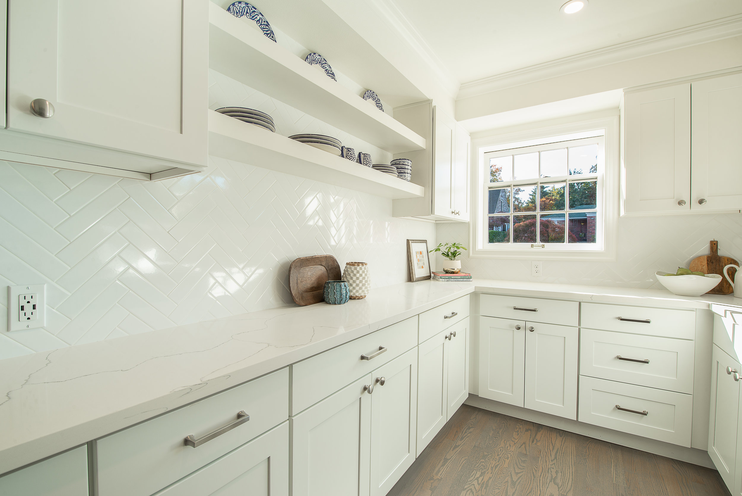 White on white: subway tiles - herringbone style, adjusted counter tops, and open shelving
