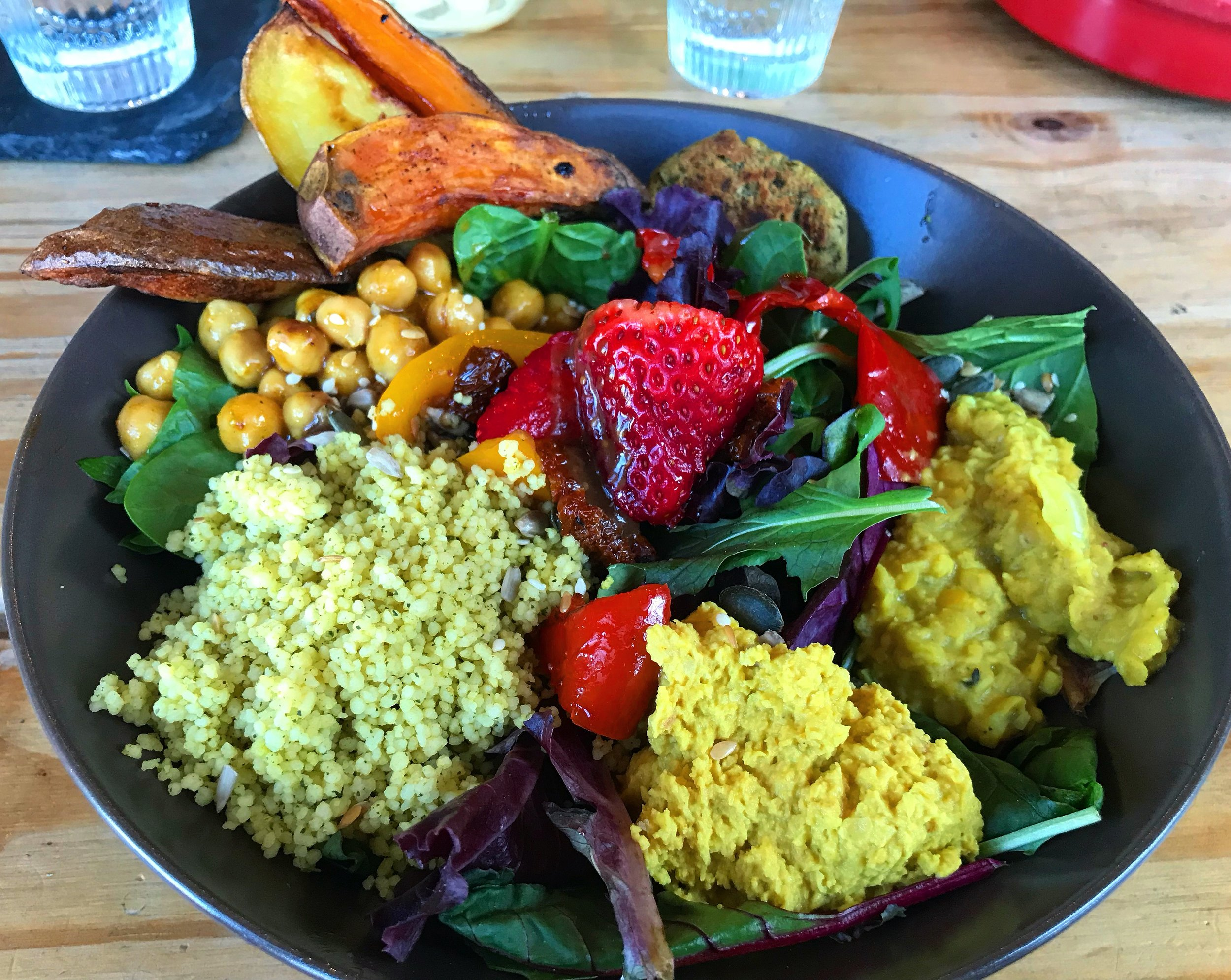 A delicious Buddha Bowl from The Green Heart, Cornwall, containing five different courses of protein (chickpeas, falafel, cous-cous, hummus & dahl-lentils).