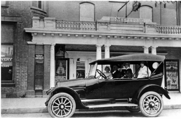 Empire Theatre. C.R. Banks, in Overland car with children, 226 Charlotte St., early 1920s. Courtesy Trent Valley Archives.