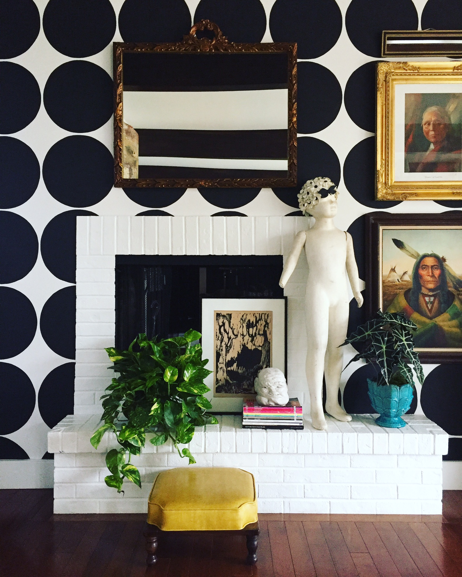 """This double-sided fireplace (other side in family Room) had horrid brown brick originally. "" says Andrea. ""After many, many coats of white paint it was transformed! Features: antique French mirror, collected art and my quirky mannequin that we've named Joey."""