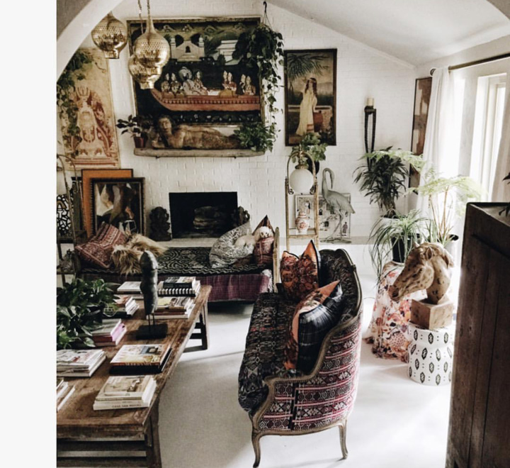 The Living Room. This is a great example of how Judy pulls off her unique style. I love that your eye does not know what to look at first; the art, the textiles, the horses head or the piles of books on the table. Gorgeous sofas and furniture, plants all add to the boho look.