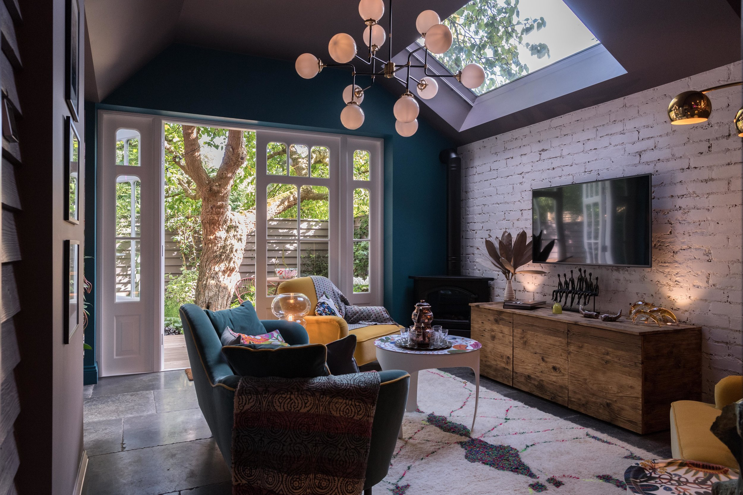Church Crescent living room chandelier and brick wall.jpg