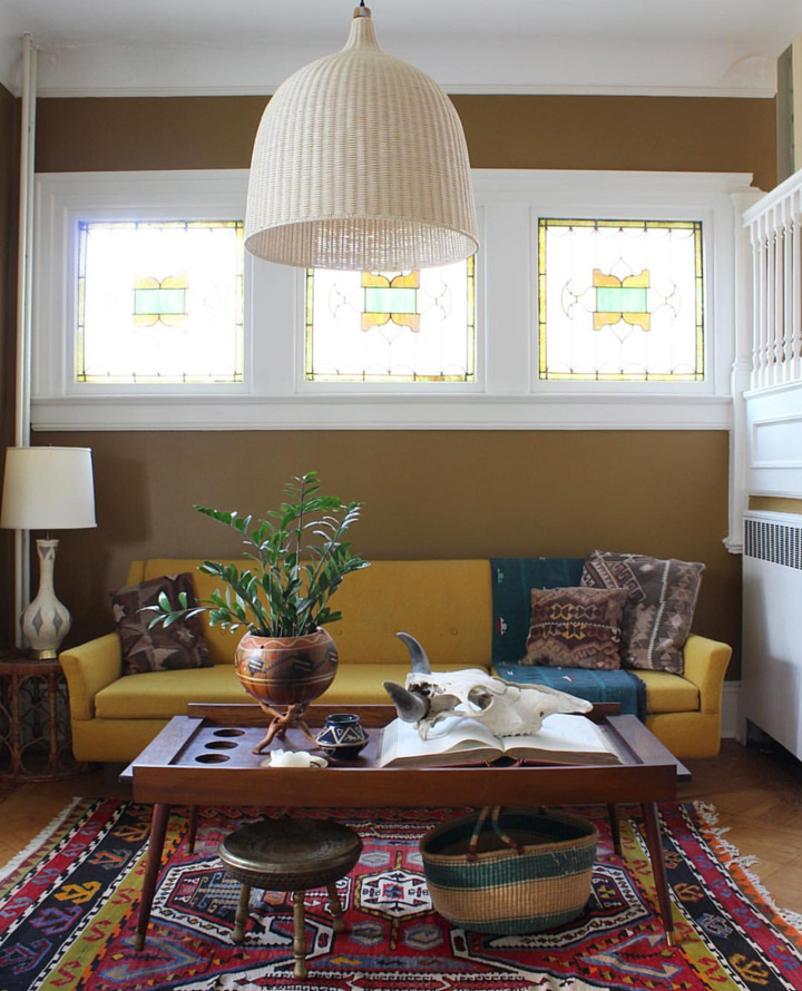 A large, bank-ledger book on the coffee table is from the 1940s and keeps a daily record of every single bank transaction made over a period of two years. The stunning yellow sofa and vibrant rug bring warmth to the room.