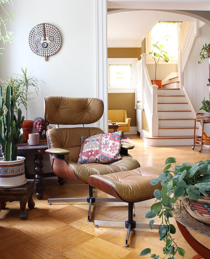 A beautiful Eames lounge chair surrounded by vintage tables and plants. You can see through into the hallway where the stained glass windows create a beautiful light and the original staircase is quite a feature.