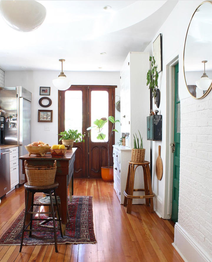 Double doors from  Amighini Architectural  at the end of the kitchen let in natural light. The kitchen lights date from the 1920s when the were used over a car lot. Mismatched kitchen furniture creates a relaxed and homely space.