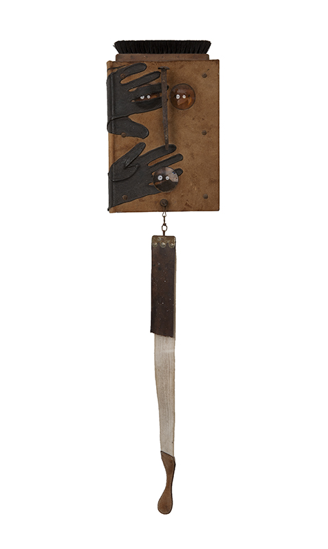 Sin título (Untitled), 1999. Object (Book, shoes brush, glass, railroad spike, fabric and leather belt, leather gloves and metal screws and hooks), 40 x 9 1/2 x 5 in.