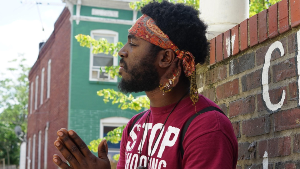 Safe Streets Baltimore is an evidence-based, public health program that works to reduce gun violence among youth. This Safe Streets volunteer, who goes by Son of Baltimore, organizes weekly block parties in McElderry Park to uplift the community (Katia Crawford).