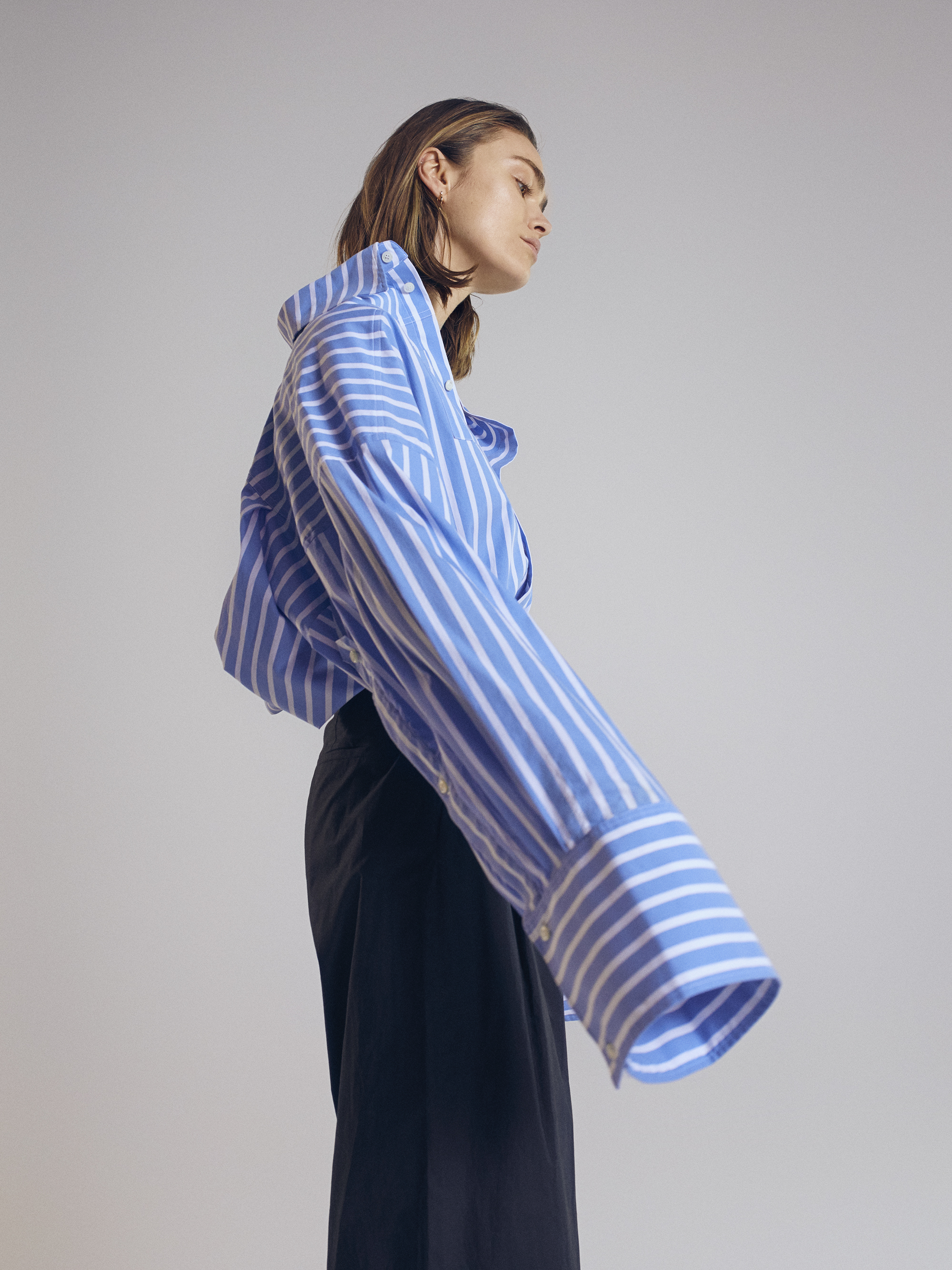 Oversized striped shirt  Schuellerdewaal . Pleated trousers  Tse.  Earring  Cos