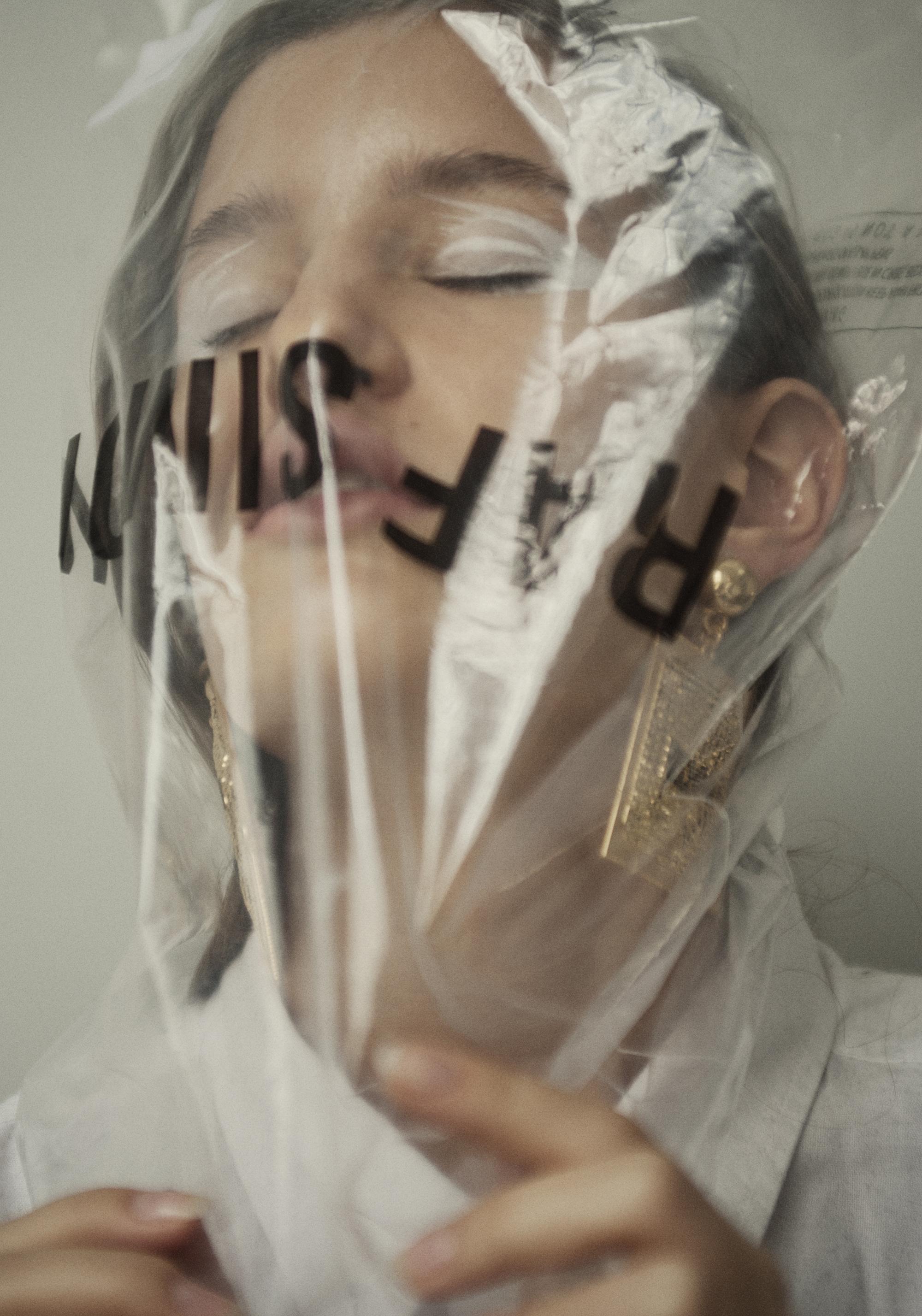 Plastic bag  Raf Simons . White shirt  Acne Studios . Earrings  Moschino X H&M