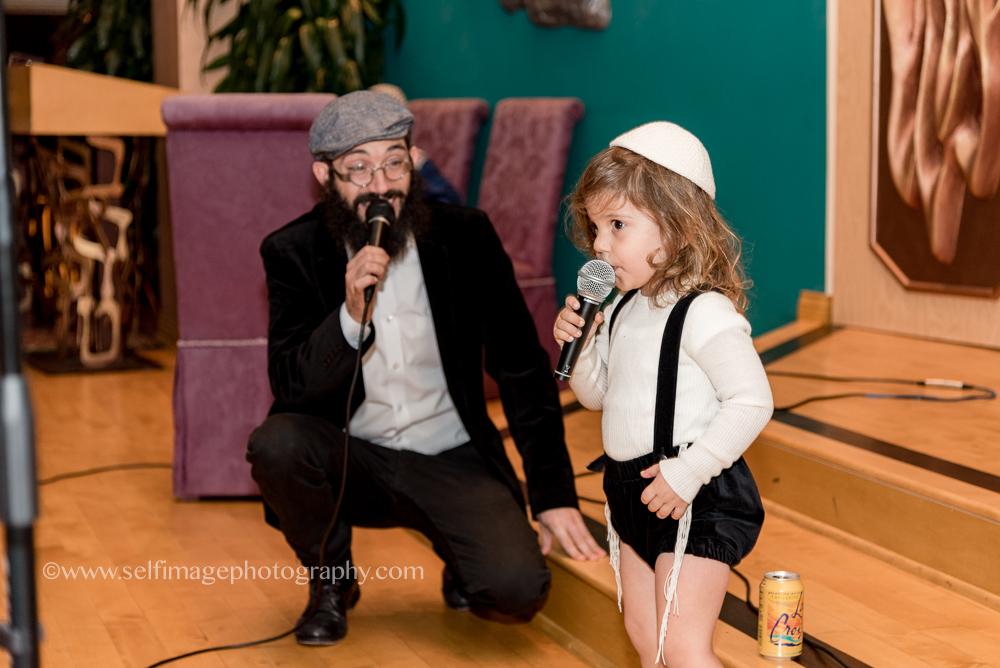 three-year-old-boy-singing-at-brithday-party