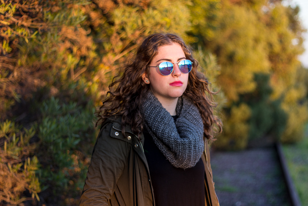 Senior Girl with sunglasses and multi colored foliage behind her