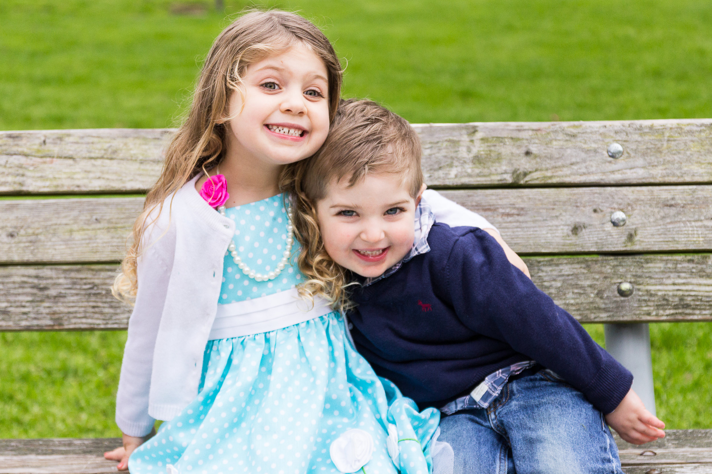4 year old girl and 4 year old brother sitting on a park bench