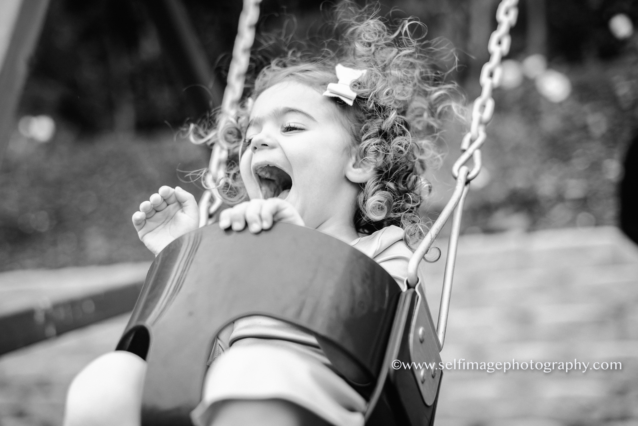 little girl laughing and swinging in her back yard
