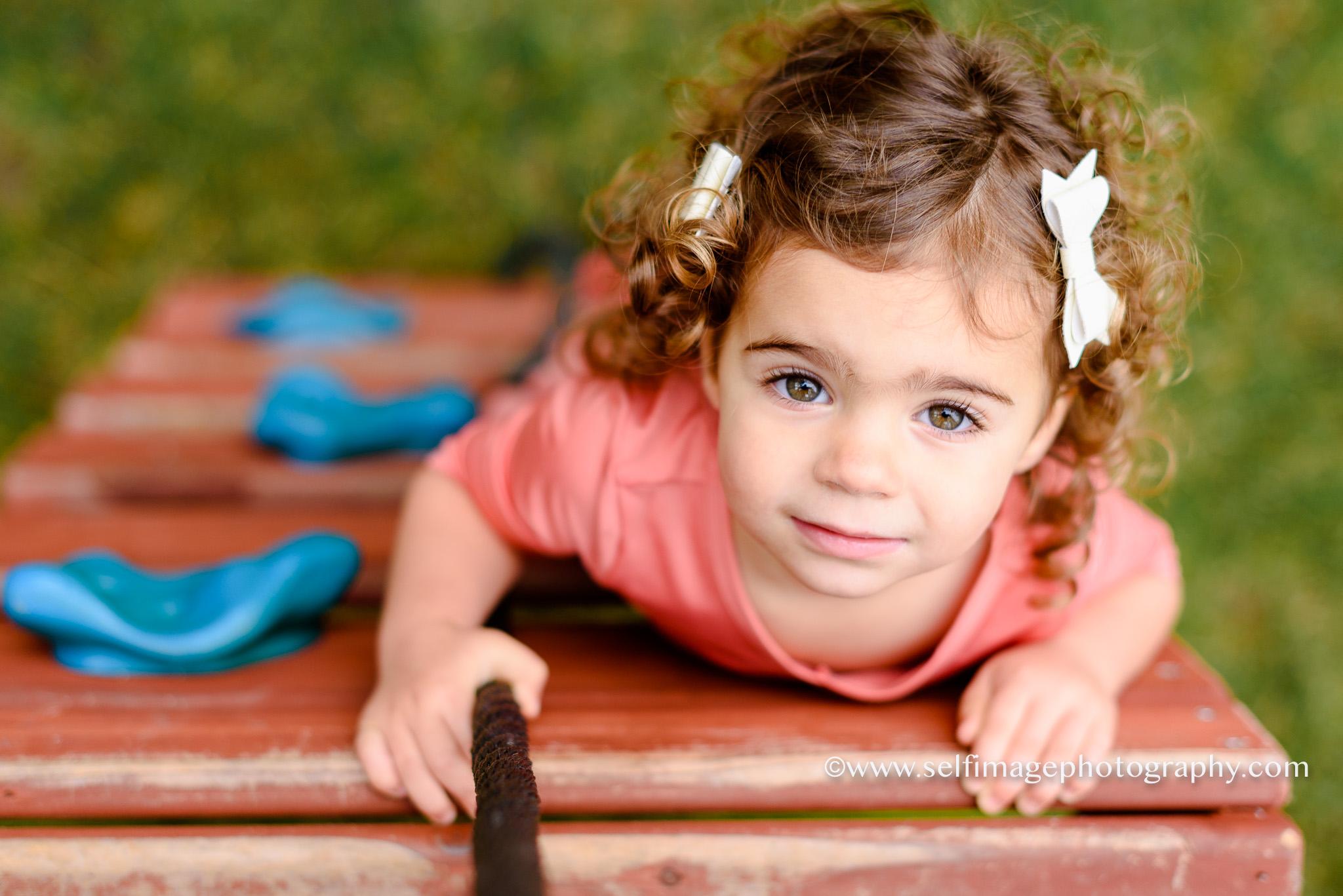 little girl climbing a play structure