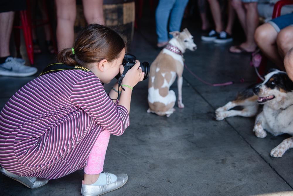girl taking photograph of dog