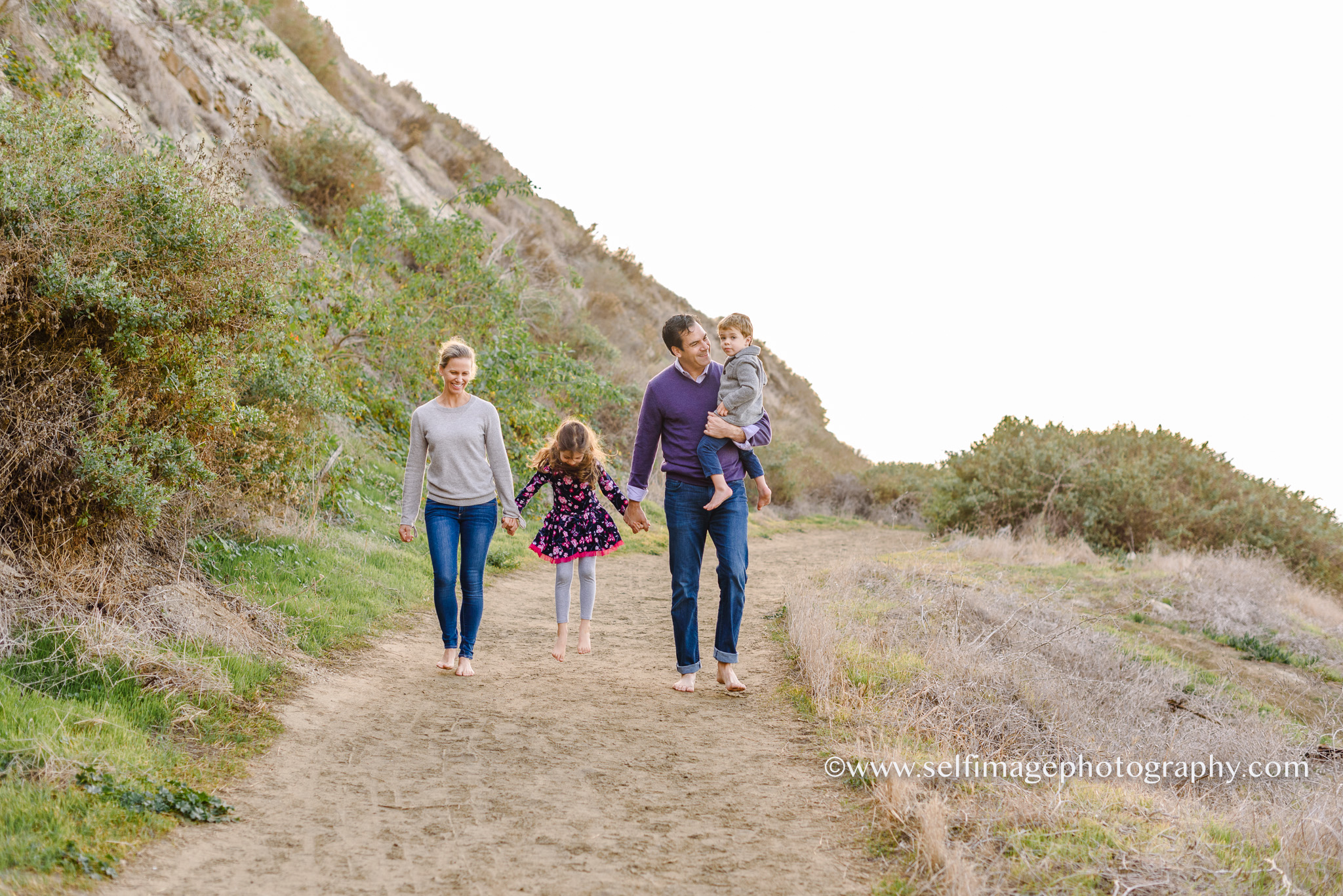 family walking on a path together while holding hands