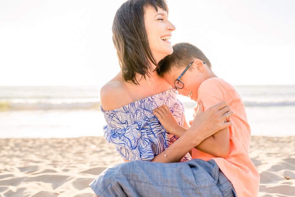 mom laughing with her son at the beach