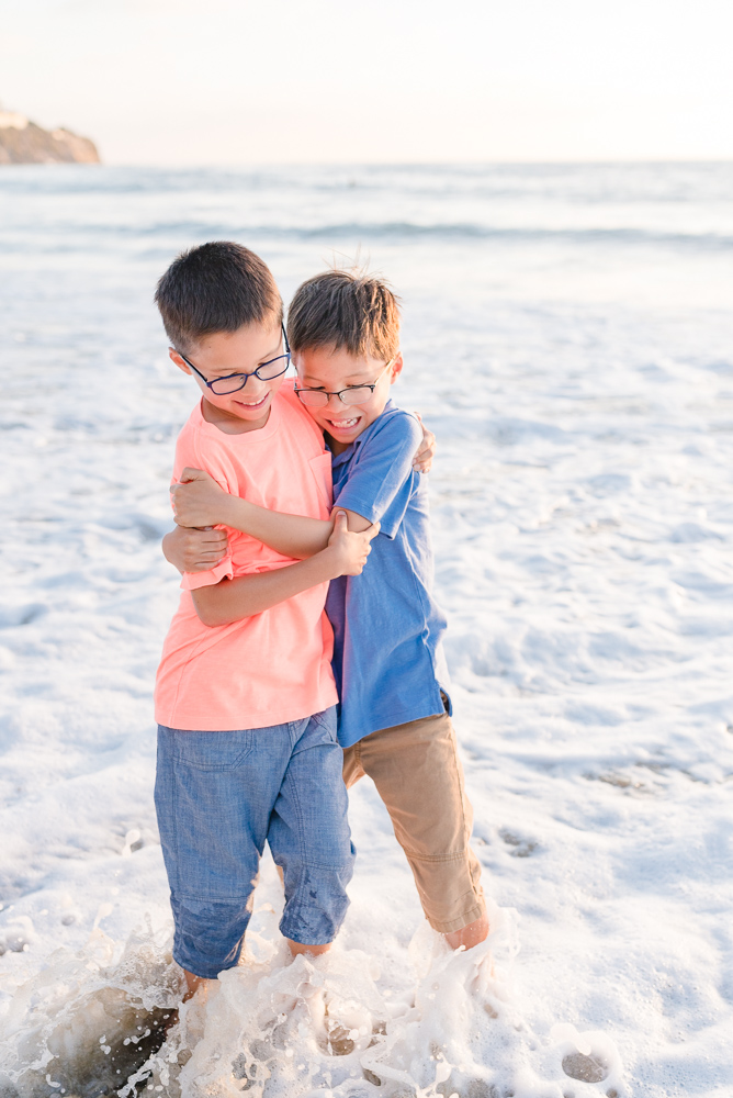 two brothers getting wet in the ocean