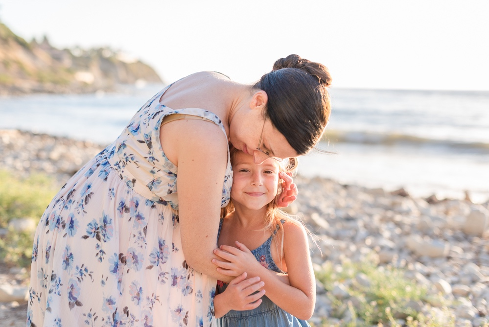 Pregnant mom and daughter hugging tenderly at the beach