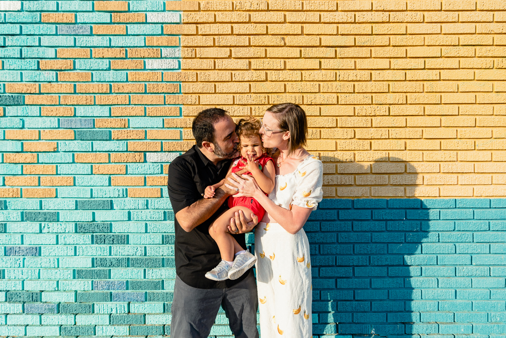 family photography,  husband and wife kissing little girl in front of a blue and yellow background