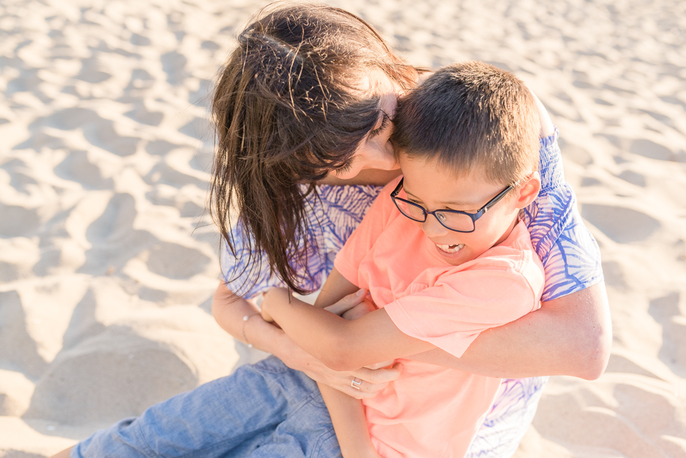 family photography,  mother kissing son on his cheek at the beach