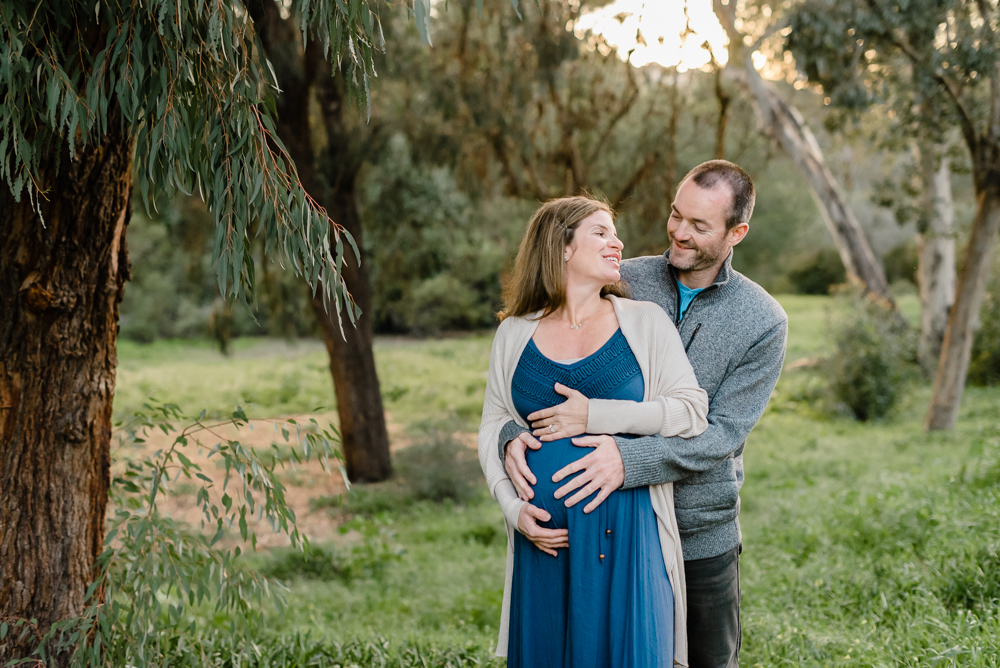 Maternity photography, couple standing by a tree