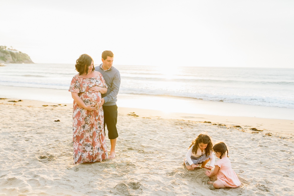 Maternity photography, mother and father watching kids play in the sand