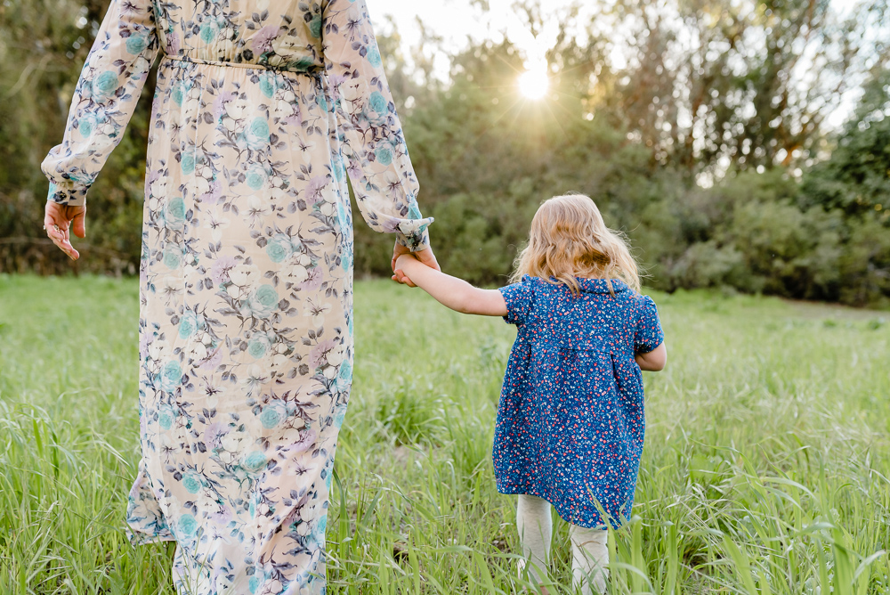 Maternity photography, mother and daughter walking in tall grass