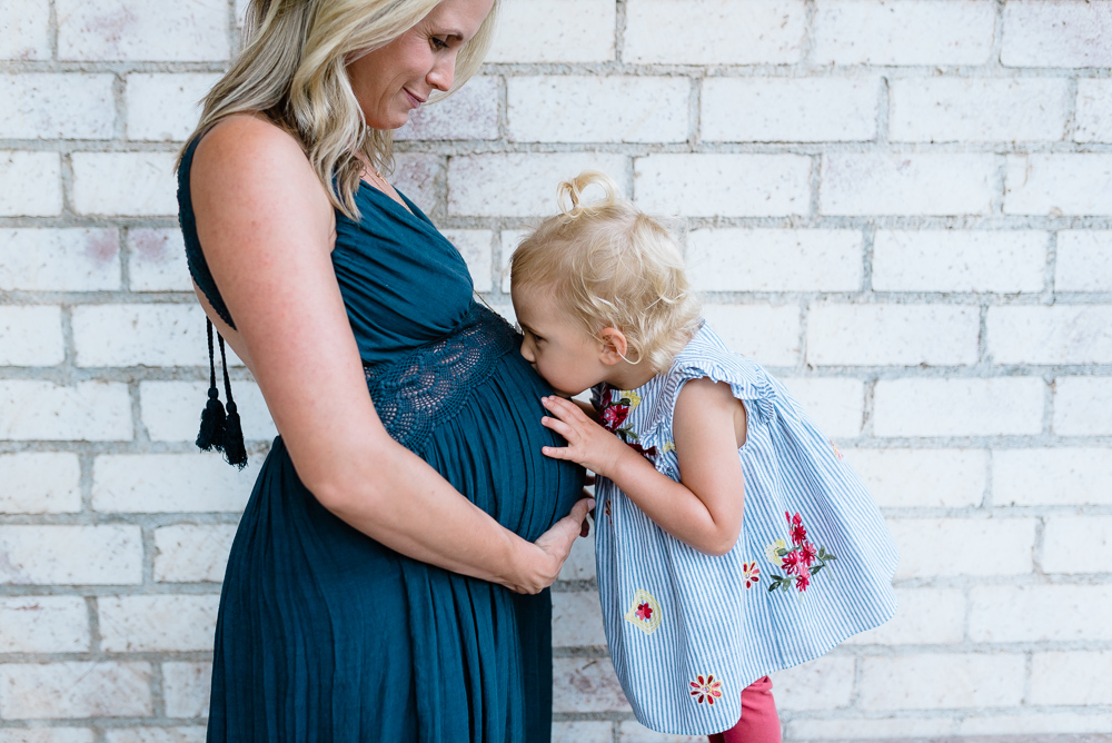 Maternity photography, girl kissing blonde mother's tummy