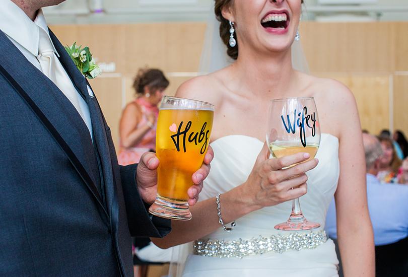 Columbus-Indiana-wedding-photographer-bride-and-groom-holding-custom-glasses-wifey-hubs.jpg