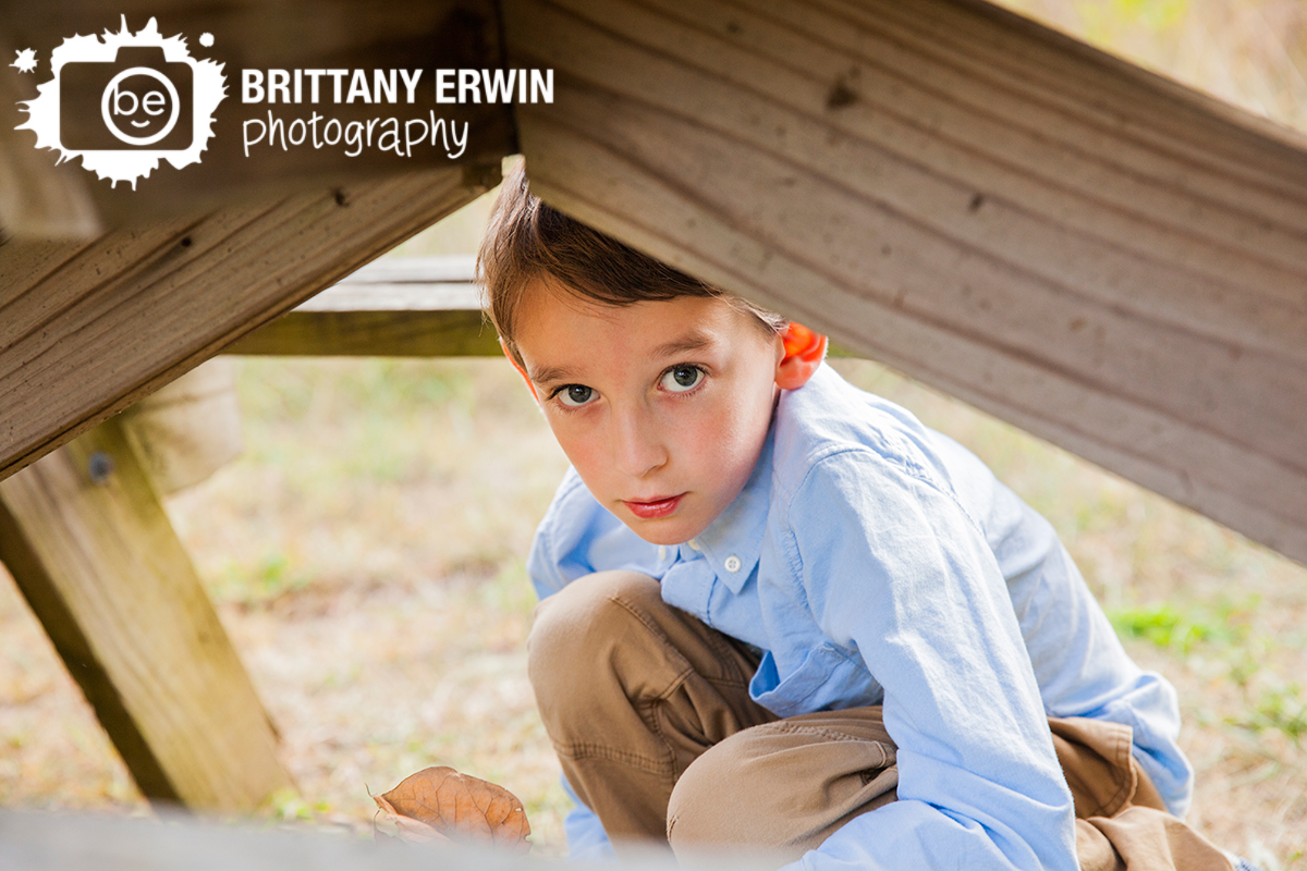 Outdoor-portrait-photographer-Zionsville-Indiana-boy-playing-under-picnic-table.jpg