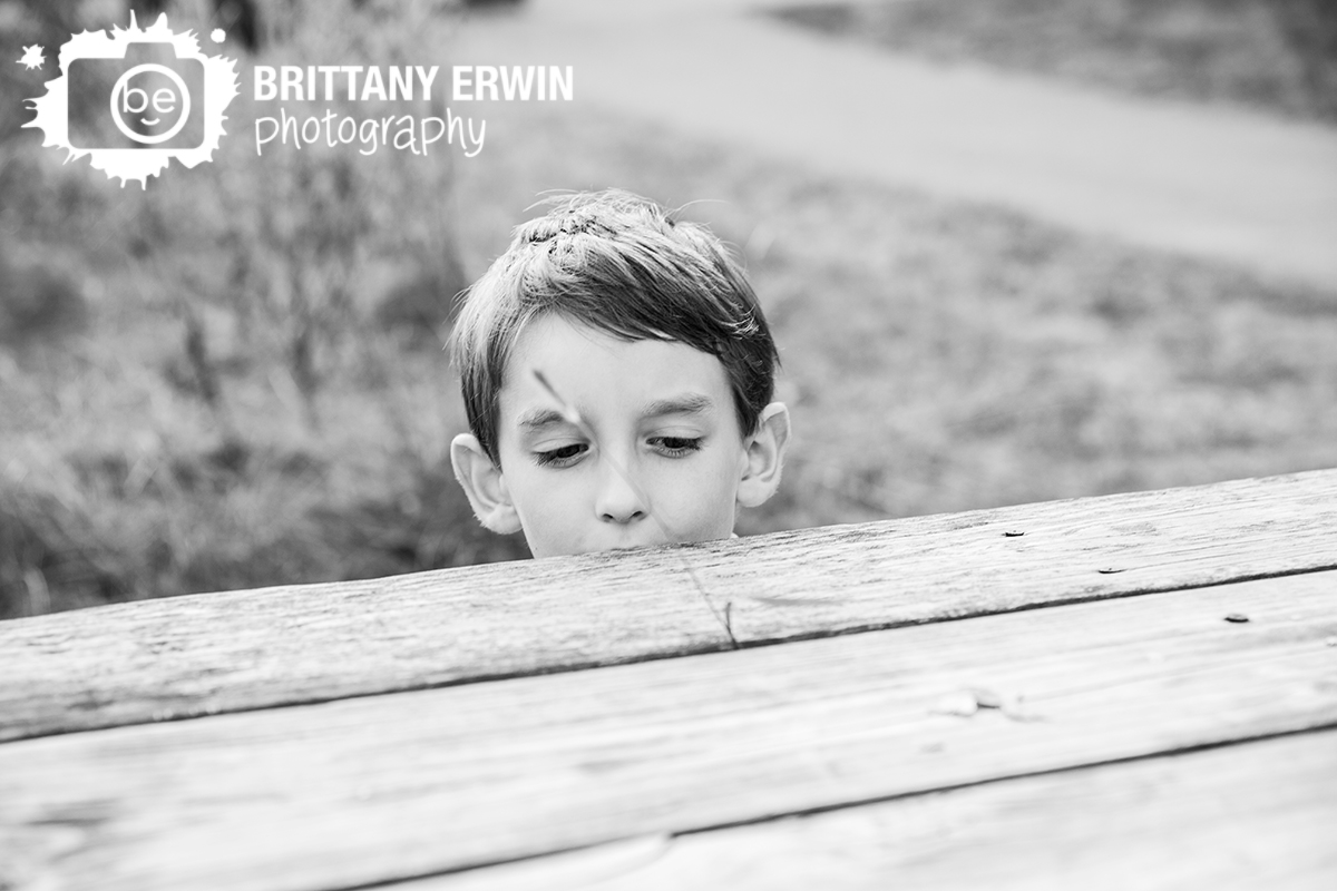 boy playing with grass and park table