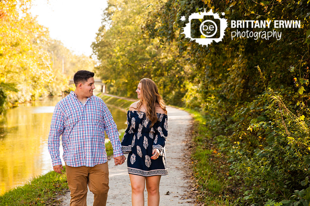 Indianapolis-proposal-photographer-couple-walk-on-path-by-canal-at-IMA-100-acres-park-bridge.jpg