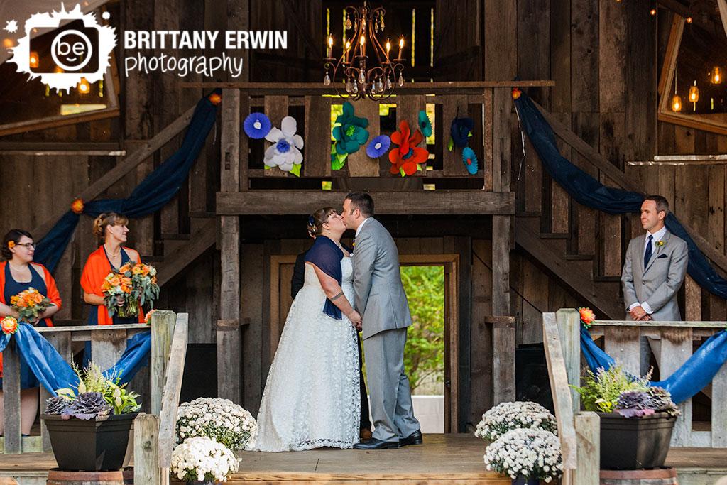 Story-Inn-barn-wedding-ceremony-paper-flower-altar-couple-first-kiss.jpg
