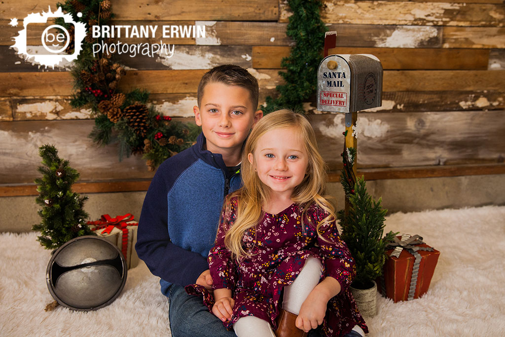 Speedway-christmas-mini-session-photographer-wreath-wood-wall-brother-sister.jpg