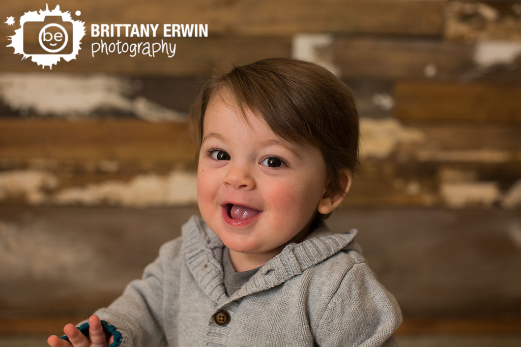 Indianapolis-studio-portrait-photographer-barn-wood-wall-baby-boy-first-birthday-sweater-smile.jpg