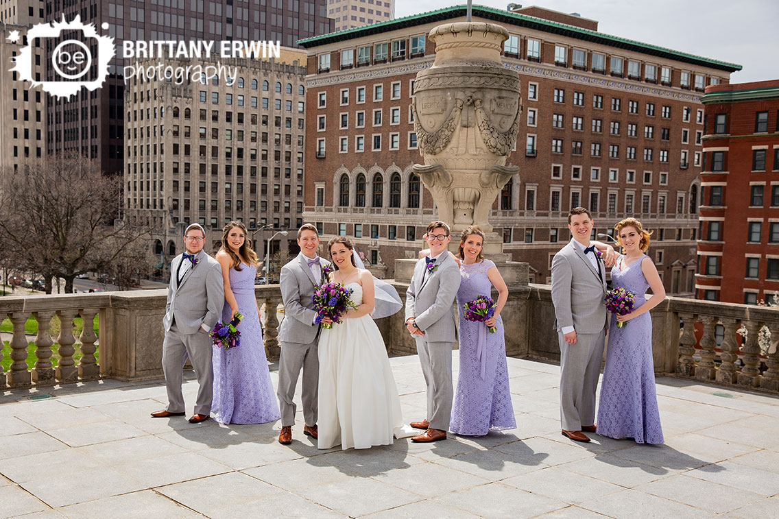 Downtown-Indianapolis-skyline-Indiana-war-memorial-bridal-party-group-creative-pose-violets-are-blue-bouquets.jpg