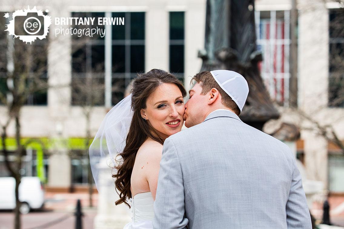 Downtown-Indianapolis-wedding-photographer-cheek-kiss-couple-on-monument-circle.jpg