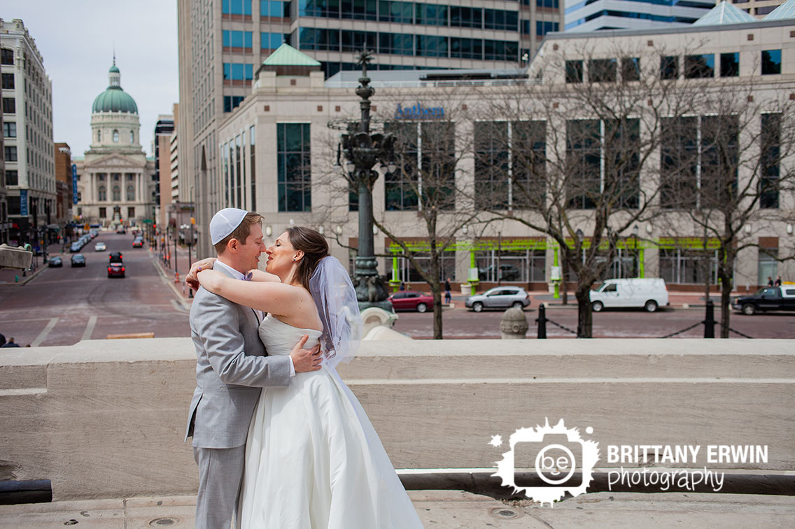 Downtown-Indianapolis-wedding-photographer-first-look-on-monument-circle-skyline-background.jpg