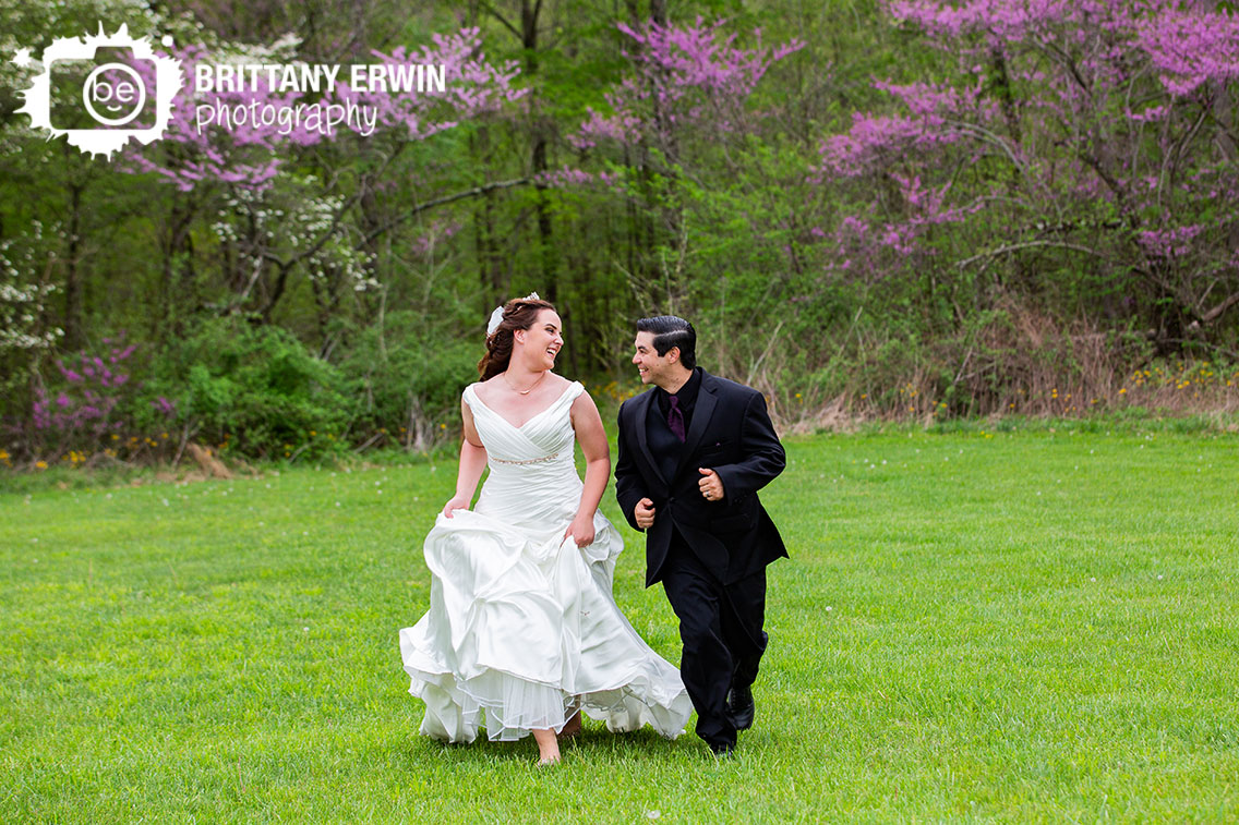 Clayshire-Castle-outdoor-wedding-venue-photographer-redbud-trees-couple-run-through-field.jpg