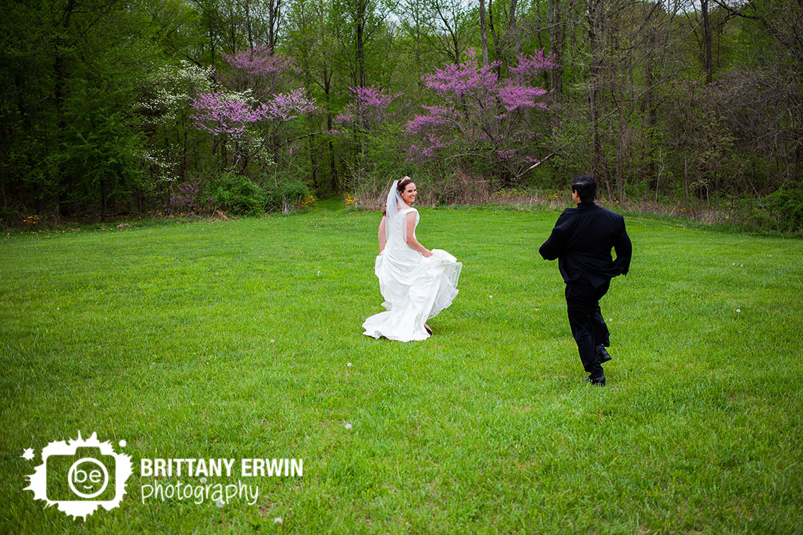 Clayshire-Castle-wedding-photographer-couple-running-through-field-redbud-trees.jpg